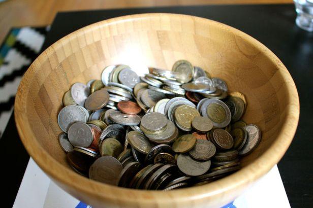 Muchas-monedas-en-un-cuenco-de-madera